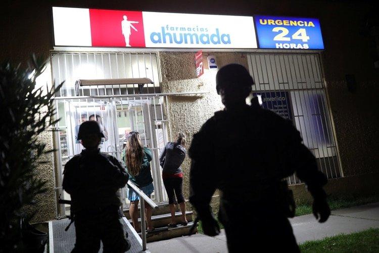 Soldados custodian una farmacia en la ciudad de Santiago de Chile el 20 de marzo de 2020 después de que el presidente Sebastián Piñera ordenara el estado de catástrofe, debido al brote de la enfermedad del coronavirus (REUTERS/Pablo Sanhueza)