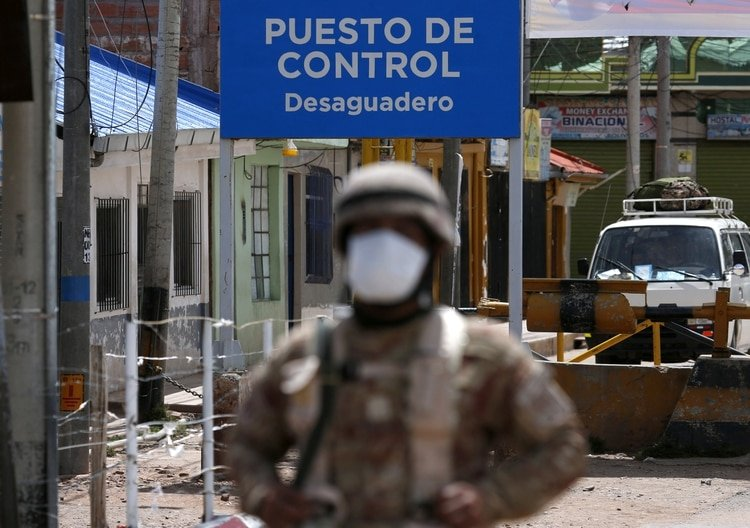 A Peruvian soldier stands at the check point in border line between Peru and Bolivia after Peru