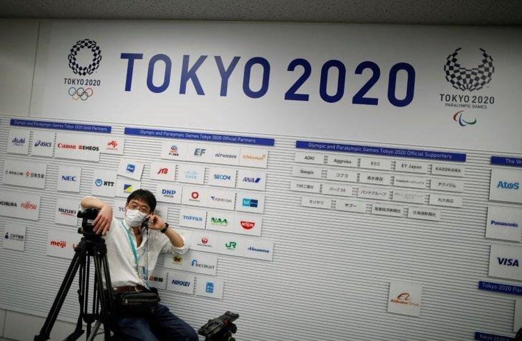 Un camarógrafo con una máscara facial protectora, frente a un cartel que muestra los logos de los Juegos Olímpicos y Paralímpicos de Tokio 2020, en el lugar de conferencia de prensa. 17 de marzo de 2020. REUTERS/Issei Kato