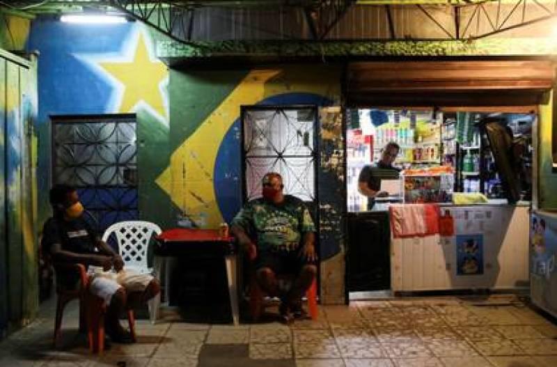 Imagen de archivo de personas que se ven en un negocio en medio de la pandemia de coronavirus, en la favela de Educandos, en Manaos, Brasil, Mayo 19, 2020. REUTERS/Bruno Kelly