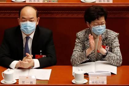 La Directora General de Hong Kong, Carrie Lam (derecha), y el Director General de Macao, Ho Iat-seng (izquierda), asisten a la sesión de apertura del Congreso Nacional del Pueblo (NPC) en el Gran Salón del Pueblo de Beijing, China, el 22 de mayo de 2020 (REUTERS/Carlos Garcia Rawlins)