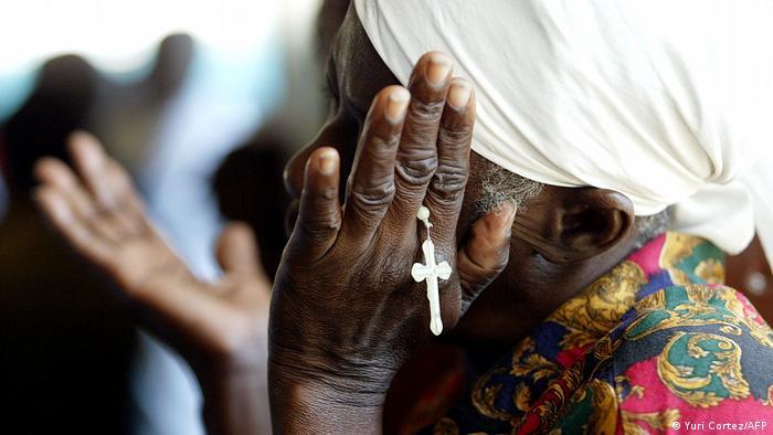 Foto simbólica de una mujer haitiana con un rosario en la mano