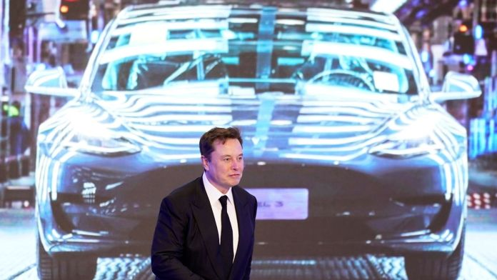 Elon Musk walks next to a screen showing an image of Tesla Model 3 car during an opening ceremony for its China-made Model Y