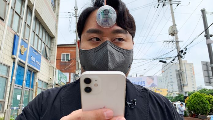 """South Korean industrial designer Paeng Min-wook showcases a robotic eye, called """"The Third Eye"""", on his forehead as he uses his mobile phone while walking on street, in Seoul, South Korea, March 31, 2021"""