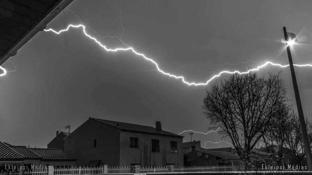 photo noir et blanc d'éclair au dessus de maisons