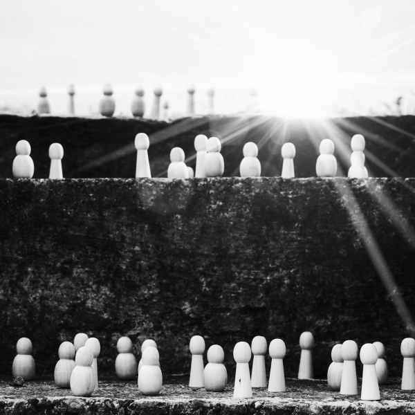 set of figurines on steps representing social ladder
