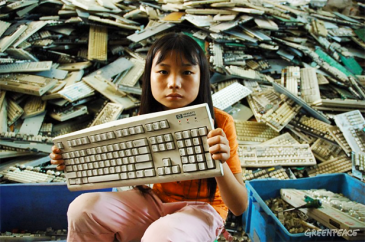 A girl with a discarded keyboard in China