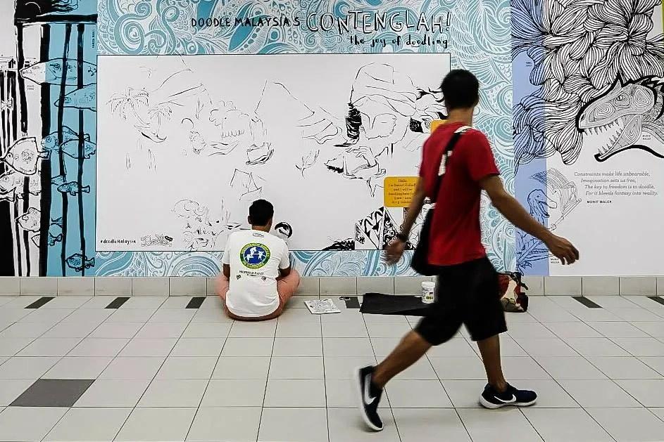 Sanuri Zulkefli busy conteng-ing one of the walls. Image credit Jahabar Sadiq.