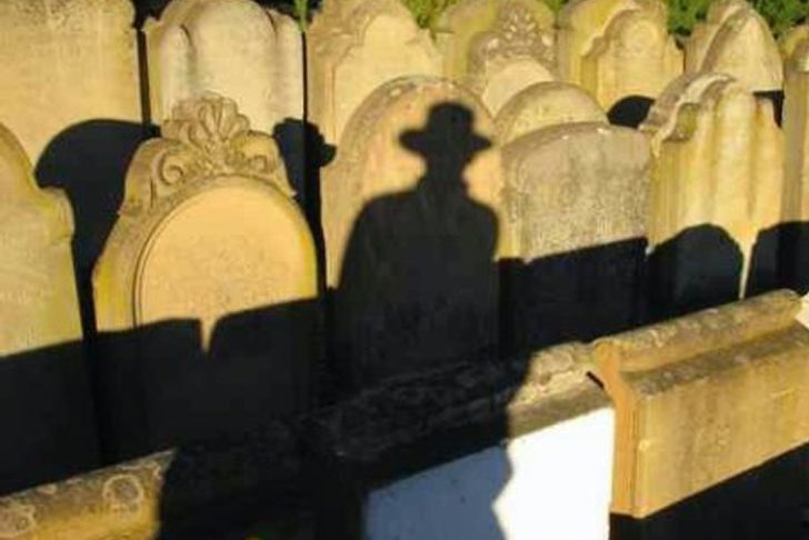 A silhouette of Tunku Halim plays on tombstones in Penang.