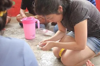 Frequent Senikami volunteer, Grace Loh, showing how to craft a whistle out of plastic straws.