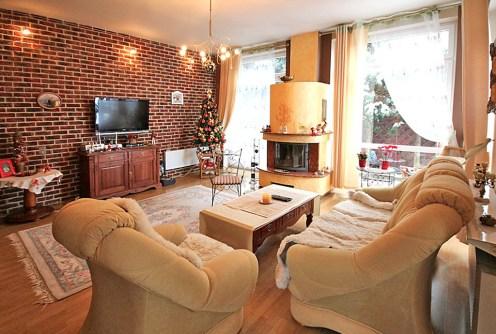 na zdjęciu salon z kominkiem w luksusowej willi na sprzedaż w Szczecinie