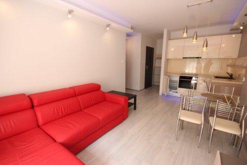 zdjęcie przedstawia widok z salonu na jadalnię i kuchnię w apartamencie na wynajem w Śródmieściu Szczecina