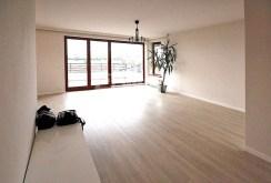 na zdjęciu przestronny salon z panoramicznymi oknami w apartamencie w Szczecinie na wynajem