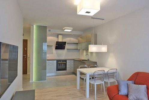 na zdjęciu widok z salonu na aneks kuchenny w apartamencie do sprzedaży w Szczecinie