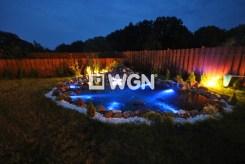 zdjęcie nocne przedstawiające zagospodarowaną i pięknie podświetloną działkę z oczkiem wodnym za willą do wynajęcia w Szczecinie