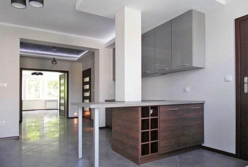 zdjęcie prezentuje widok od strony salonu na aneks kuchenny w apartamencie do sprzedaży na Mazurach