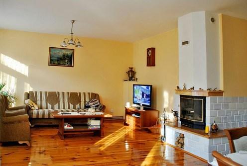 zdjęcie prezentuje salon z kominkiem w luksusowej willi do sprzedaży w okolicach Warszawy