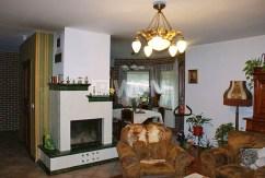 na zdjęciu komfortowy salon z kominkiem w ekskluzywnej willi na sprzedaż w okolicach Warszawy