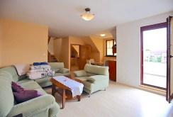 na pierwszym planie komfortowy salon, na dalszym kuchnia w luksusowym apartamencie w Szczecinie na wynajem