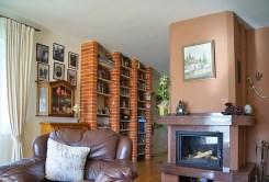 zdjęcie przedstawia komfortowy salon z kominkiem w luksusowej willi do sprzedaży na Mazurach