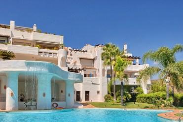 widok od strony basenu na apartamentowiec w Costa del Sol, Marbella (Hiszpania), w którym znajduje się oferowany na sprzedaż luksusowy apartament