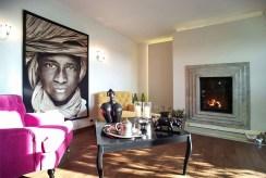 zbliżenie na kominek w salonie luksusowego apartamentu na sprzedaż Łódź