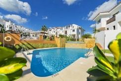 widok na osiedle z basenem, na którym znajduje się oferowana na sprzedaż luksusowa willa Hiszpania (Costa del Sol, Kadyks)