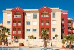 rzut od strony basenu na luksusowy apartamentowiec, w którym mieści się ekskluzywny apartament na sprzedaż Los Alcazare (Hiszpania)