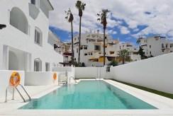 widok na basen przy ekskluzywnym apartamencie na sprzedaż Hiszpania
