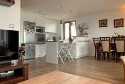 przestronne wnętrze i widok na aneks kuchenny w luksusowym apartamencie na sprzedaż Konin