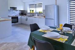 na pierwszym planie jadalnia, w oddali kuchnia w ekskluzywnym apartamencie na wynajem Szczecin