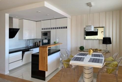 zaprojektowane zgodnie z nowoczesnymi trendami wnętrze aneksu kuchennego w ekskluzywnym apartamencie do wynajmu Mazury