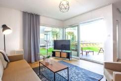 na pierwszym planie salon i wyjście na taras przy luksusowym apartamencie na sprzedaż nad morzem