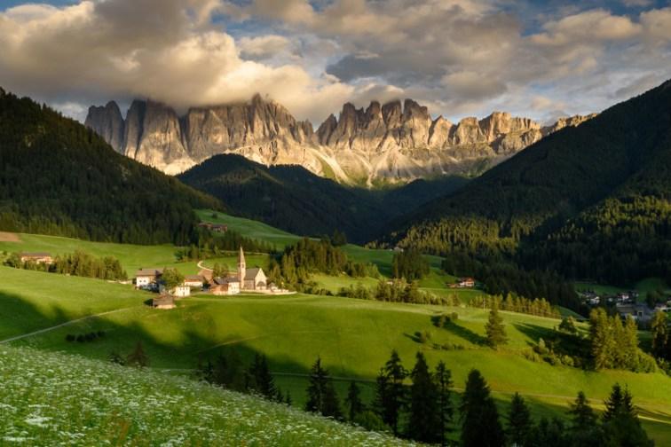 Nummer 4 - Dolomieten, uitzicht op een vallei met  een kerkje met daar achter een imposante bergketen.