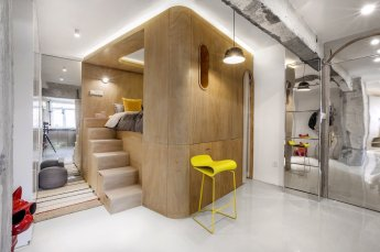 the-bed-is-flanked-by-two-staircases-one-of-which-is-hidden-behind-a-white-curtain-hidden-storage-is-integrated-into-the-stair-design