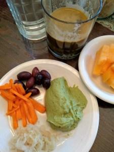 Avocado Hummus with carrot sticks, olives, sauerkraut, cantaloupe, and some yummy juice