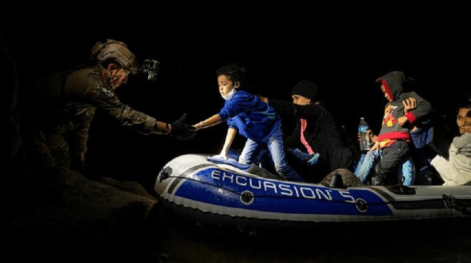 Migranți care solicită azil coboară dintr-o barcă gonflabilă