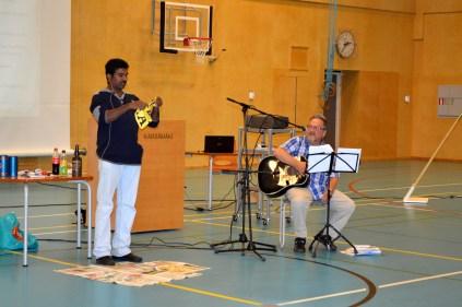 Tarinaniskentäkilpailuun osallistunut S.V. Dhanamurthy tekemässä tauon jälkeen taikatemmpuja. Kuvassa myös yleisöä laulattanut opettaja Teuvo Marttila. Kuva Eero Mattila