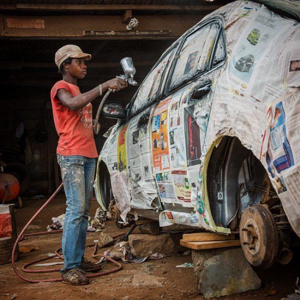 Una joven pinta un coche con spray en Tarkwa, Ghana. Foto: Nana Kofi Acquah / EverydayAfrica.