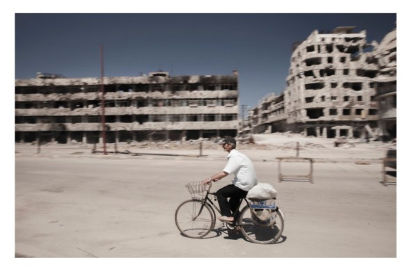 Un hombre pasea en bicicleta rodeado de ruinas. Foto: Carole Alfarah (EFTI).