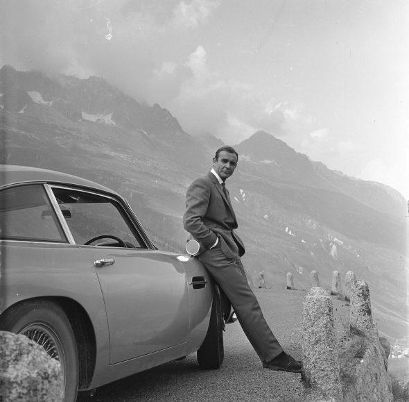 SEAN CONNERY se relaja apoyado sobre su Aston Martin DB5 durante el rodaje de escenas de Goldfinger en los Alpes suizos. Copyright Notice – © 1964 Danjaq, LLC and United Artists Corporation. All rights reserved.