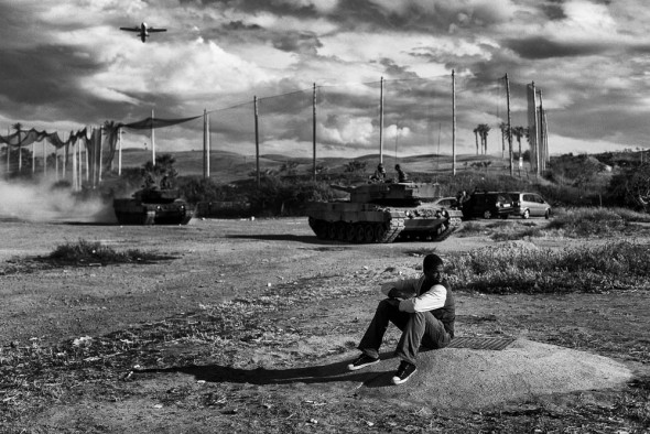 Melilla, Spain April 21st 2014. A young migrant from Mali sits in front of the C.E.T.I while at his back, a couple of tanks of the Spanish army are doing a practice.