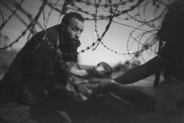 World Press Photo del Año Noticias de actualidad. Primer Premio. Fotografías individuales. Foto de Warren Richardson (Australia). Esperanza para una nueva vida. Frontera Serbia/Hungría, 28 de agosto de 2015. Un bebé es entregado a través de un agujero en una valla de alambre de púas a un refugiado sirio que ya ha logrado cruzar la frontera entre Serbia y Hungría, cerca de la localidad húngara de Röszke.