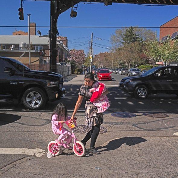 Una madre latina ayuda a su hija a cruzar la calle en Jackson Heights, Queens, Nueva York. Foto: Ana Nance.