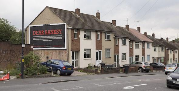 Anuncio en el barrio londinense de Hackney invitando a Banksy a participar en el festival Meninas de Canido.
