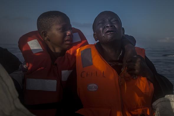 Una niña de 11 años de nigeria, a la izquierda, que aseguró que su madre había muerto en Libia, llora junto a su hermano de 10 años al ser recatados de una patera repleta de inmigrantes. Foto: Santi Palacios/Associated Press.