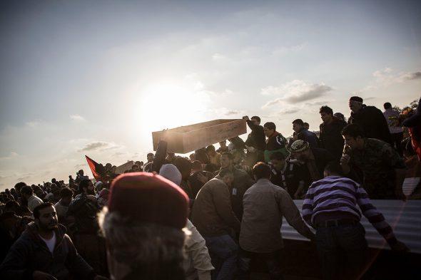 Civiles sostienen un ataúd vacío durante el funeral de varios cadáveres pertenecientes a combatientes rebeldes y civiles ejecutados por el ejército libio y enterrados en una fosa común cerca de Brega durante la guerra civil de 2011. Benghazi, Libia, 2012. Foto: Manu Brabo.