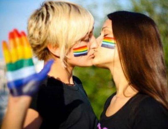 Dos mujeres se besan con la bandera del arcoíris.