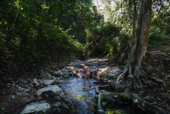 November 09, 2014. Felipe Ruiz, de 65 años, camina todos los días una hora de ida y otra de vuelta desde su casa hasta un lavadero natural donde, entre árboles y matorrales, se asea y limpia sus ropas. (Lavadero El Caballo, Nejapa, El Salvador). ©Calamar2/ Pedro ARMESTRE