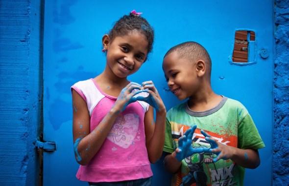 Dos niños en Brasil colaboran en la pintura de un mensaje.
